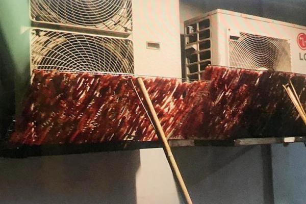 Raw meat being dried on air con vent outside Beach Road HDB flat