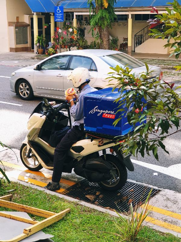 SingPost postman having lunch on his bike evokes sympathy